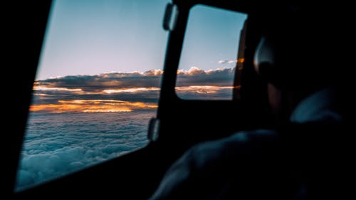 Silhouette of pilot controlling airplane while flying high above fluffy clouds in sky