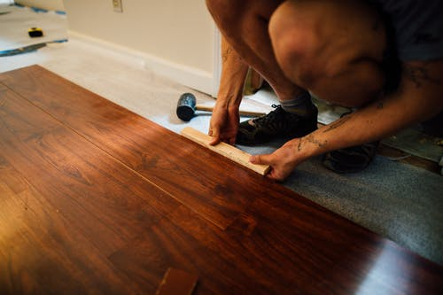 Crop man installing laminate flooring
