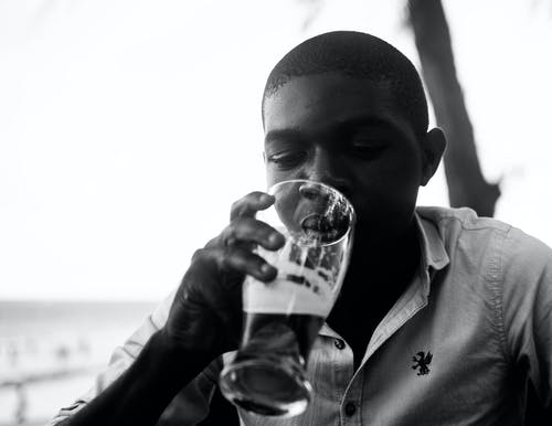 Man Drinking from Clear Drinking Glass