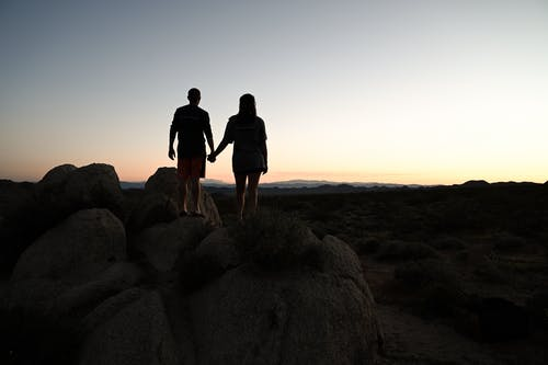 Man and Woman Standing on Rock Formation during Sunset