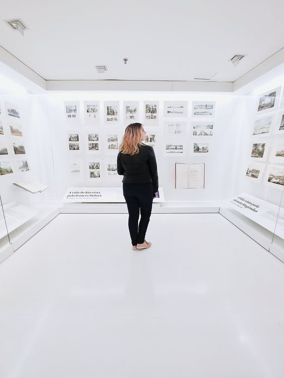 Woman standing in modern museum with pictures on walls