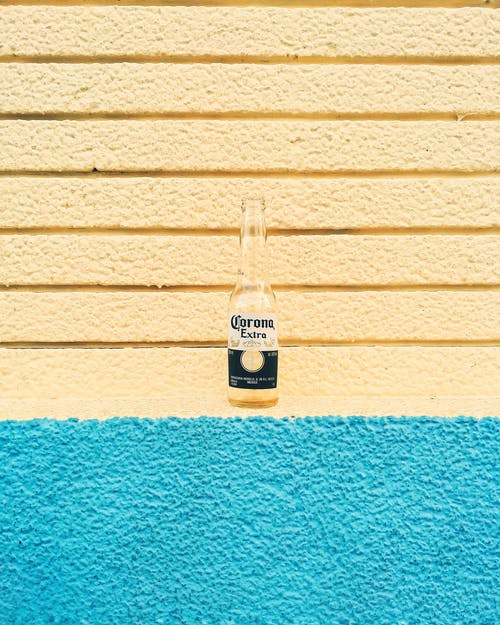Empty glass bottle of beer placed against yellow wall with blue surface below