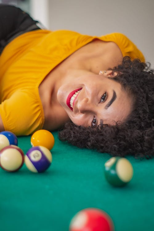 Happy young ethnic woman on pool table