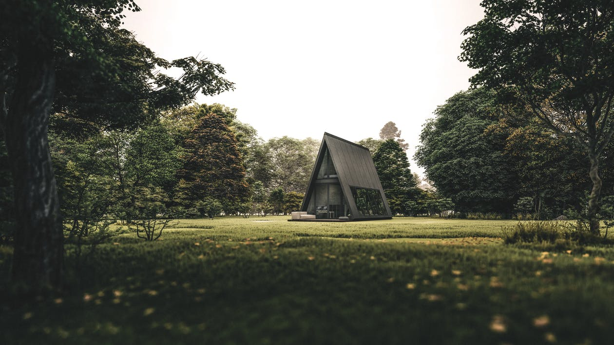 Exterior of rural creative cottage in shape of triangle located on grassy lawn in abundant forest