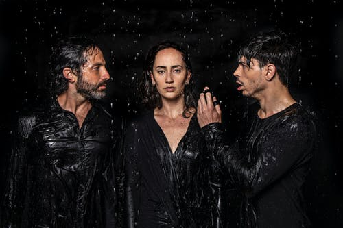 Photogenic talented artists wearing wet black clothes standing in studio under water drops