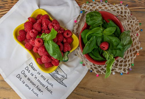 Overhead Shot of Raspberries and a Bowl of Basil Leaves