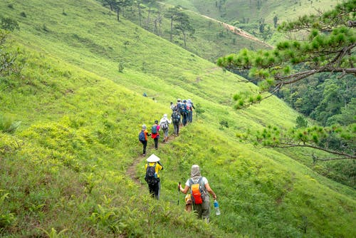 Unrecognizable travelers walking on path along slope of mountain