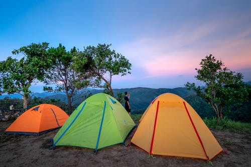 Colorful tents located at camp in mountainous valley near green trees against picturesque sunset sky