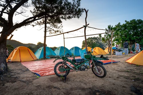 Tents and motorbike in camp in nature
