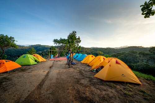 Campground with colorful tents placed on top of mountain in picturesque highlands on sunny day