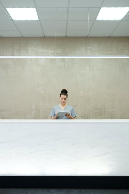Woman Employee Standing behind Front Desk