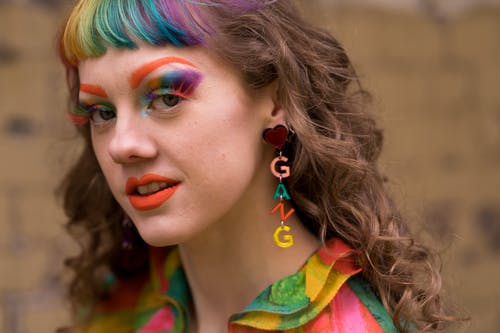 Young eccentric female with rainbow bang and makeup in trendy clothes and gang letter earrings standing on street and looking at camera