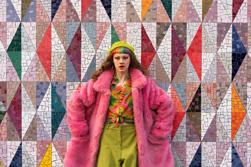 Confident young lady in trendy clothed and pink fur coat standing against abstract geometric wall with hands in pockets and looking at camera