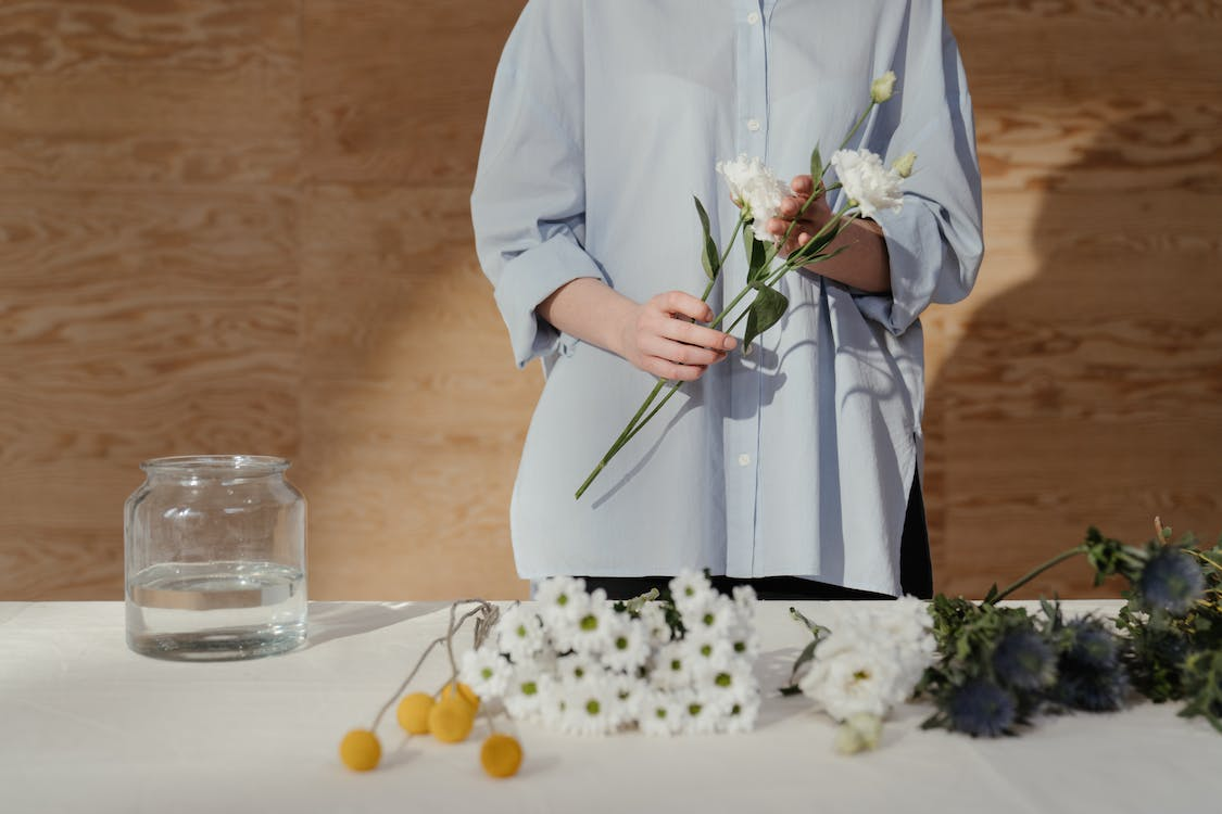 Woman in White Long Sleeve Dress Holding White Flowers