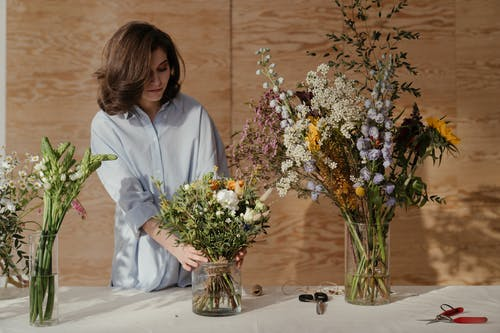 Woman in White Dress Shirt Holding Bouquet of Flowers