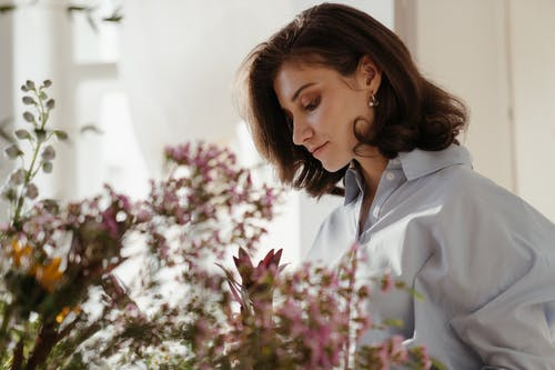 Woman in White Blazer Looking at Pink Flowers