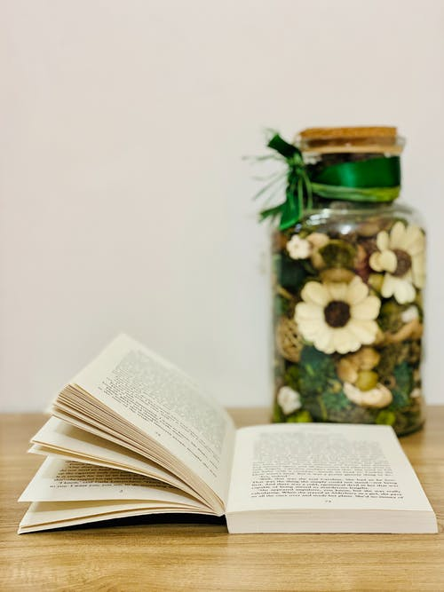 Glass jar with decorative flowers and plants on wooden table composed with opened book at home