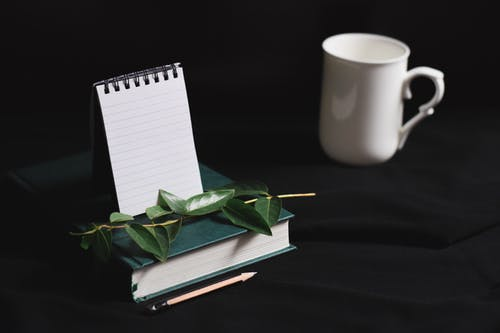 White cup and notepad arranged with book and green leaves on black table