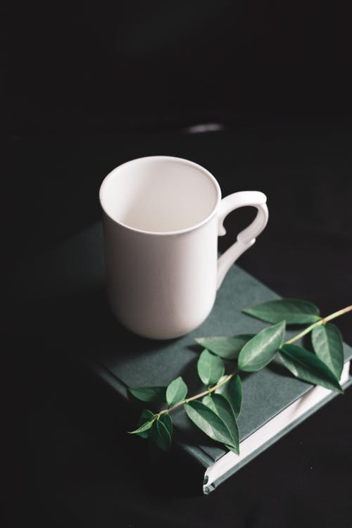 White mug composed with book and green leaves placed on black table