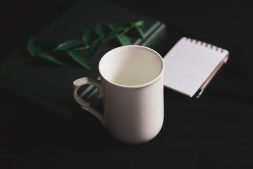 Composition of white mug and notebooks