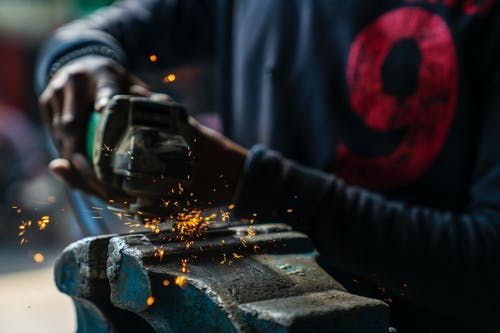Crop faceless professional African American craftsman wearing dirty clothes welding metal details in industrial workshop