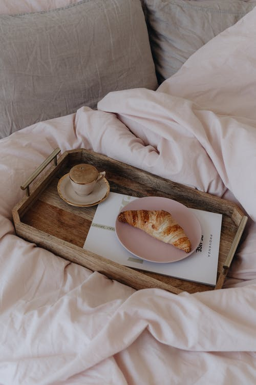 A Croissant and a Cup of Coffee on a Wooden Tray