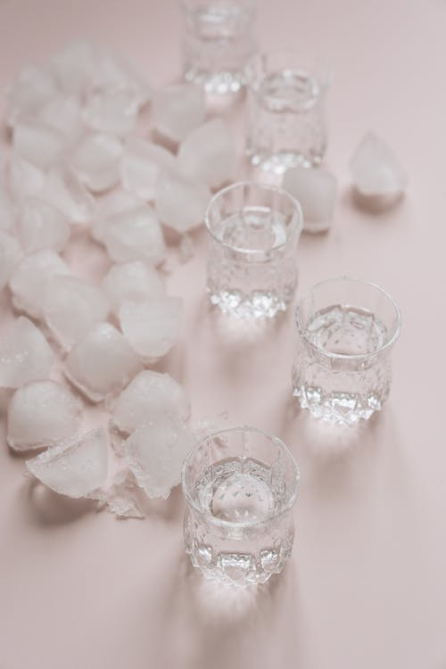 Clear Drinking Glasses on Pink Surface