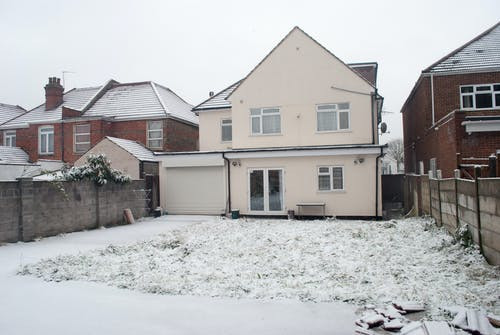 Exterior of residential houses in village community on snowy terrain during freezing wintertime