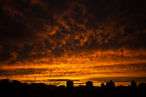 Silhouettes of contemporary town buildings located under majestic cloudy sunset sky of bright orange color
