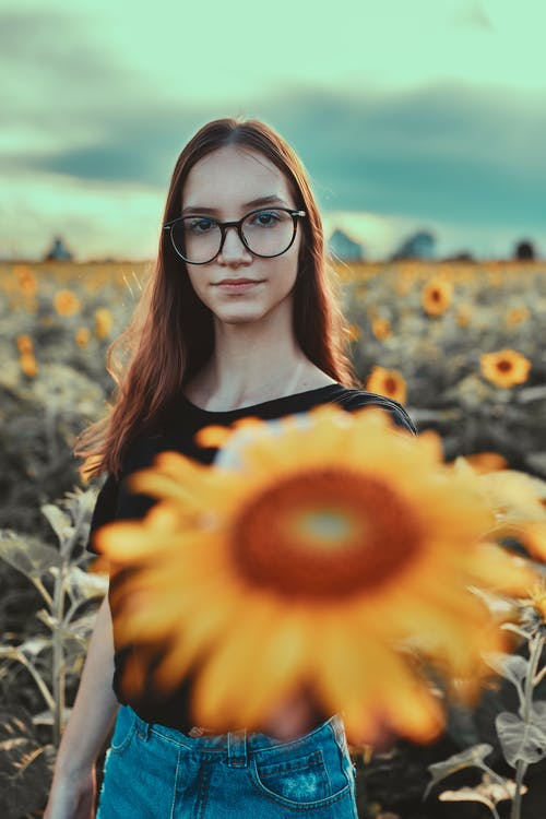 Woman in Black Framed Eyeglasses and Black Shirt Standing on Yellow Sunflower Field