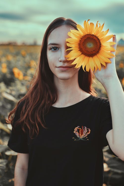 Woman in Black Crew Neck T-shirt Holding Sunflower