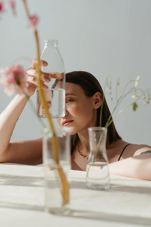 Woman in Black Brassiere Holding Clear Glass Bottle