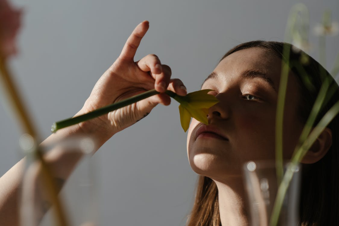 Woman Holding While Smelling Yellow and Green Flower