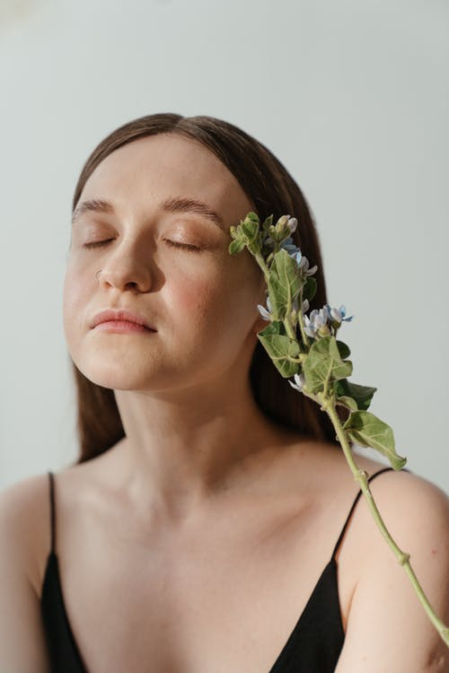 Woman in White Spaghetti Strap Top With White Flower on Ear