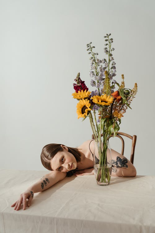 Woman Lying on Bed With Yellow Flowers on Her Head