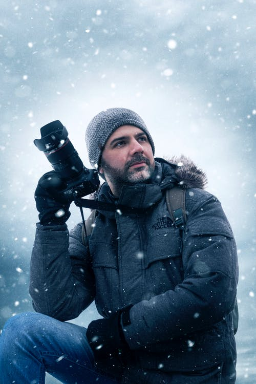 Man in Winter Jacket Holding Black Dslr Camera