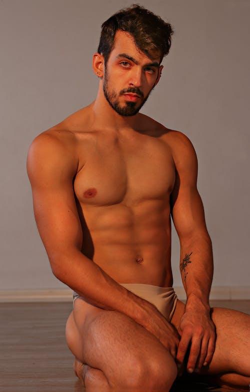 Confident athletic male in skin color underwear sitting on floor in studio