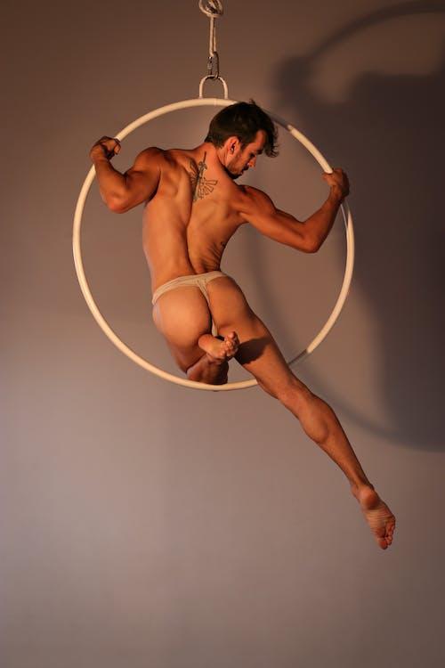 Powerful male acrobat performing on gymnastic circle