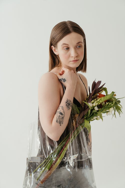 Woman in White Tank Top Holding Green Plant