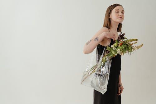 Woman in Black Sleeveless Dress Holding White Flowers