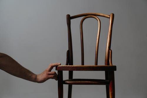 Person Sitting on Brown Wooden Chair