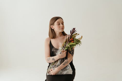 Woman in Black Tank Top Holding Green Plant
