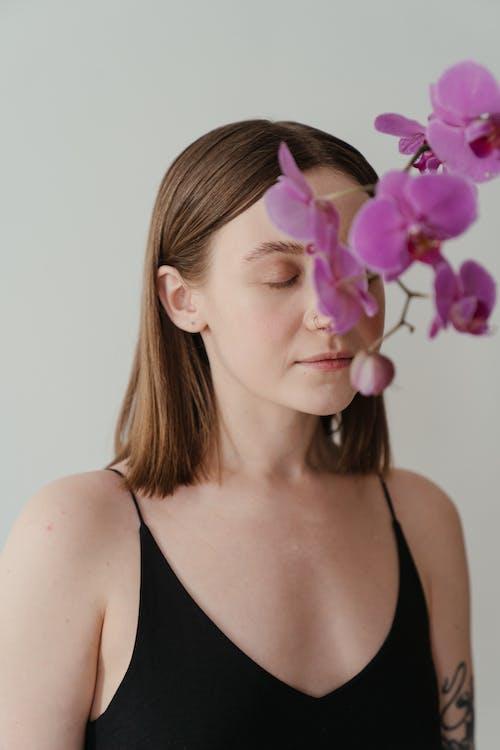 Woman in Black Tank Top With Purple Flower on Her Ear