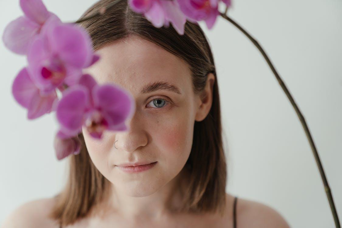 Woman With Purple Flower on Ear