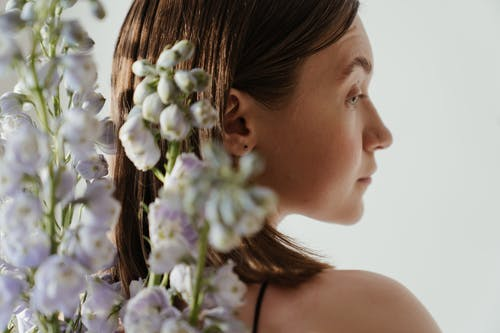 Woman With White and Purple Flowers on Her Ear