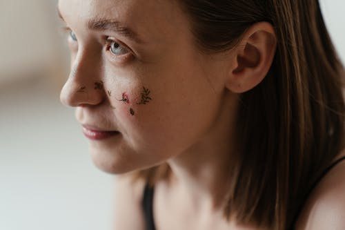 Close-Up Photo of Woman With Floral Art Tattoo on Her Face