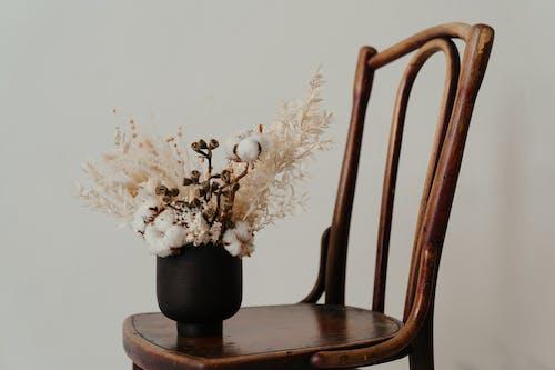 White Flowers in Black Ceramic Vase on Brown Wooden Chair