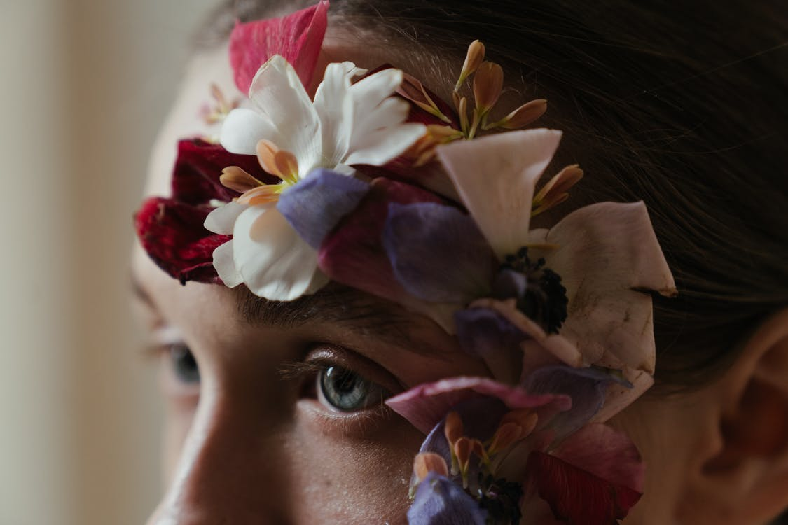 Woman With White and Purple Flower on Her Ear