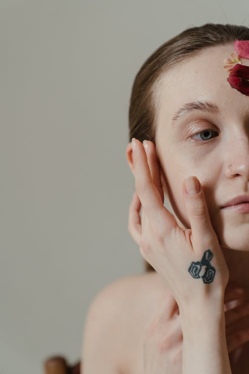 Woman With Black and Red Floral Tattoo on Her Left Hand