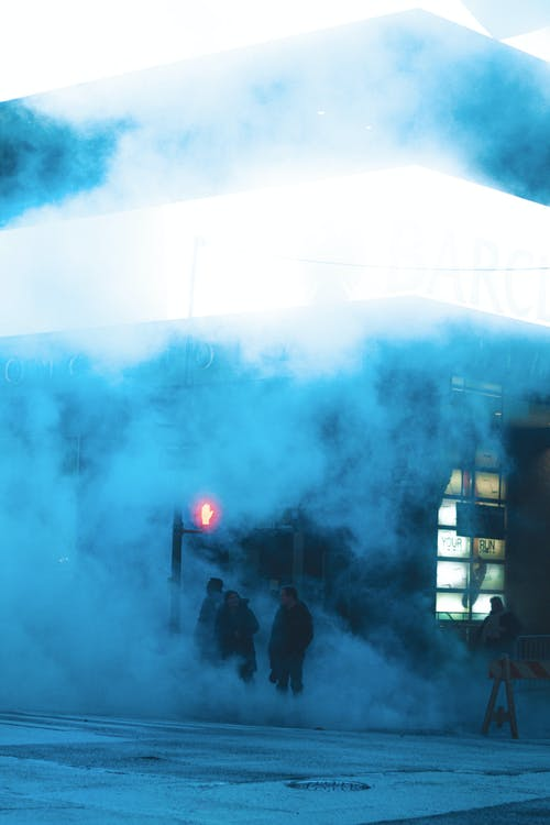 Pedestrians near traffic lights on night street covered with smoke